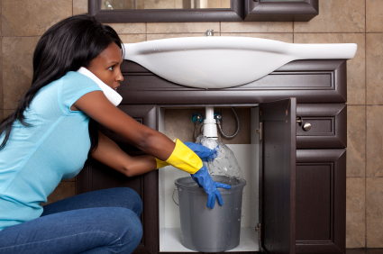 Lady trying to stop a leaking sink drain